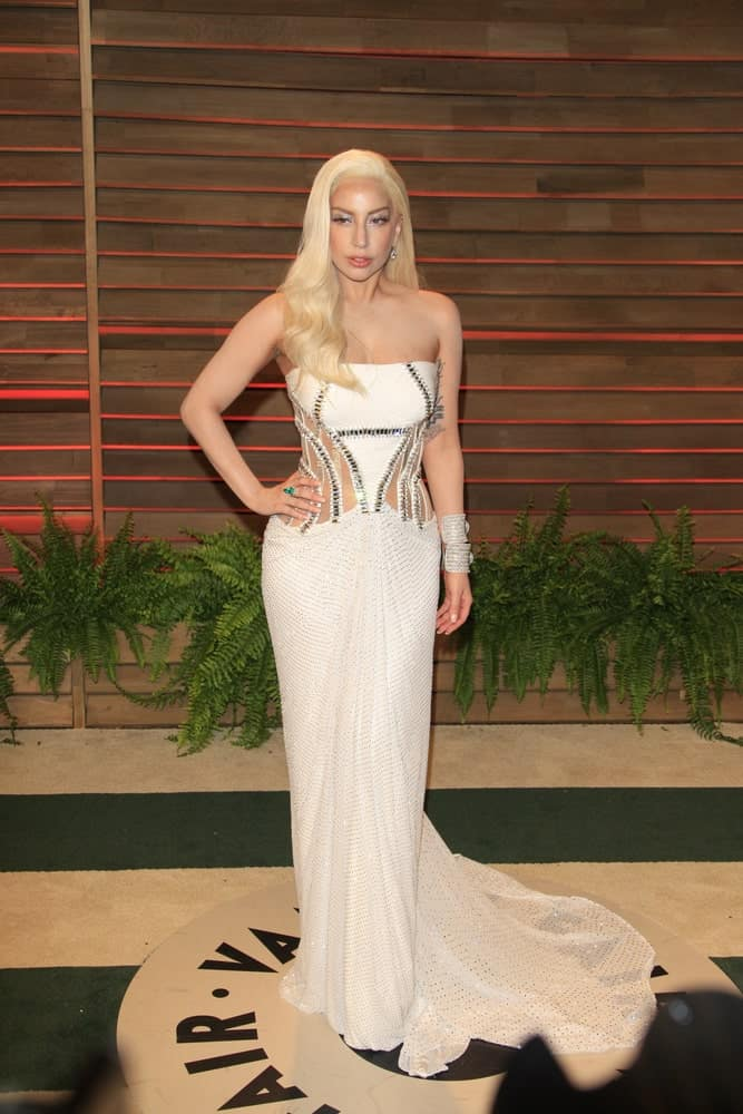 Lady Gaga attended the 2014 Vanity Fair Oscar Party at the Sunset Boulevard on March 2, 2014 in West Hollywood, CA. She was a picture of sophistication in her long white dress and side-swept light blond long hairstyle with waves at the tips.