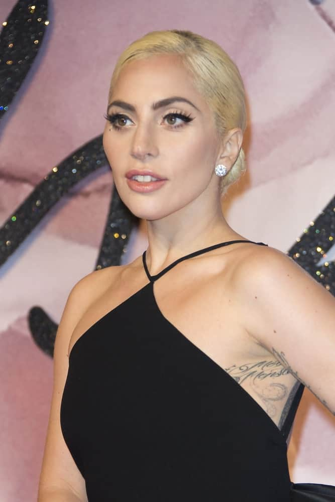 On December 5, 2016, Lady Gaga attended The Fashion Awards 2016 in London, United Kingdom. She came with a simple yet classy black dress that emphasizes her elegant neckline together with her slick blond low bun hairstyle.