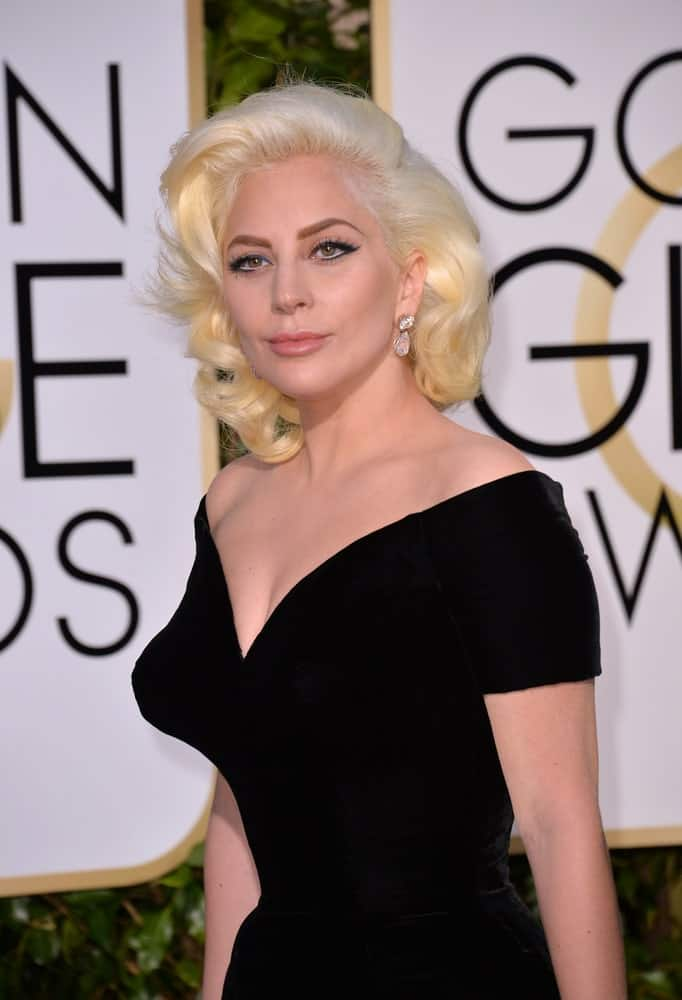 On January 10, 2016, Lady Gaga attended the 73rd Annual Golden Globe Awards at the Beverly Hilton Hotel. She wore a classy vintage black dress that complemented her white blond side-swept curls with subtle highlights.