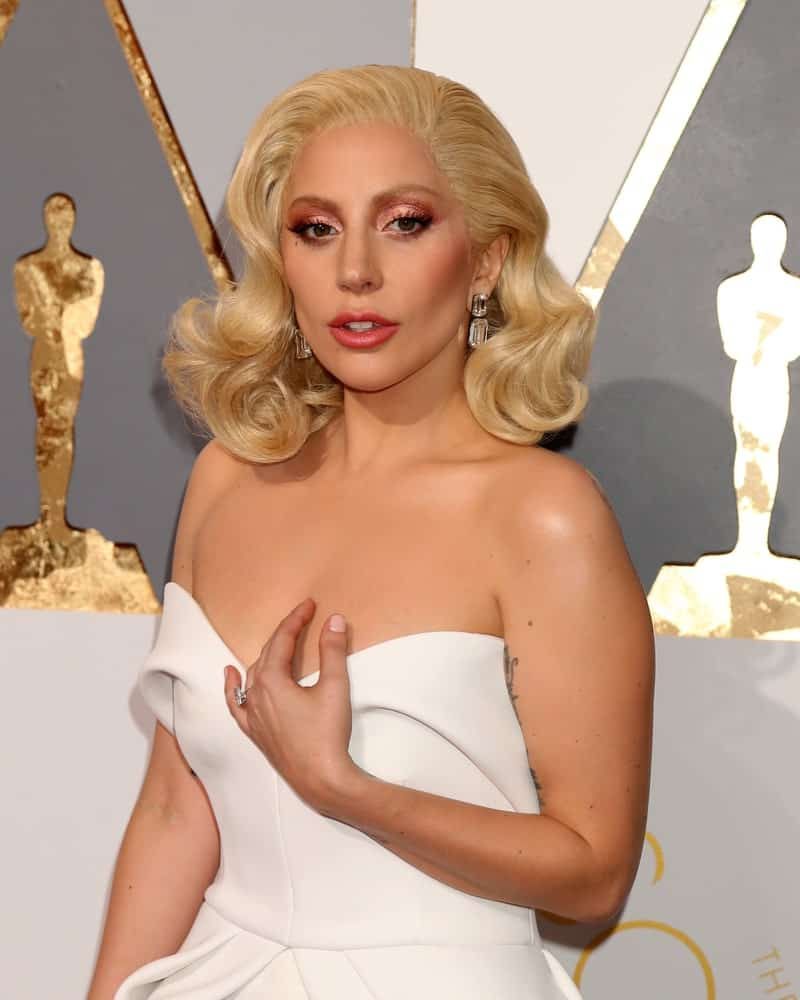 Lady Gaga attended the 88th Annual Academy Awards at the Dolby Theater on February 28, 2016 in Los Angeles, CA. She paired her lovely white strapless dress with a vintage look on her white blond hair that was styled into side-swept large curls.