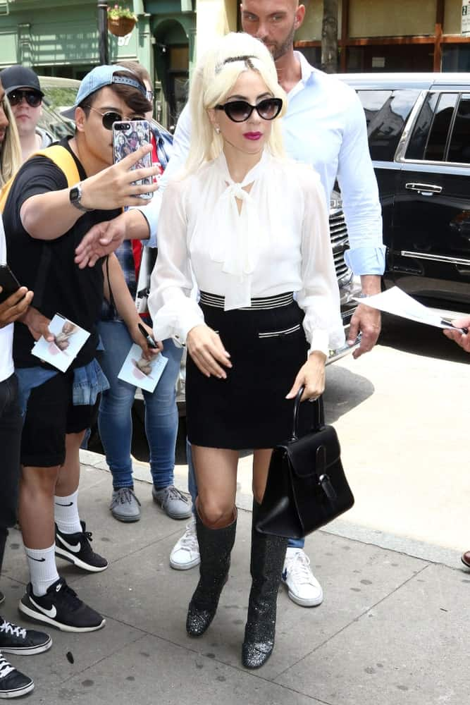 On May 26, 2018, Lady Gaga was seen walking the streets of New York City. She was lovely in her white buttoned blouse and short skirt to pair with her cool sunglasses and white blond ponytail with curtain bangs.