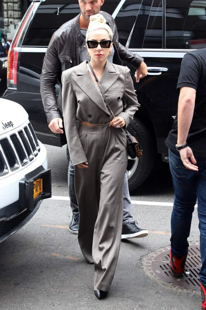 On May 28, 2018, Lady Gaga was seen on a fine New York City day walking the streets wearing a gray pantsuit that she paired with a brown belt, black sunglasses and an elegant top knot hairstyle.