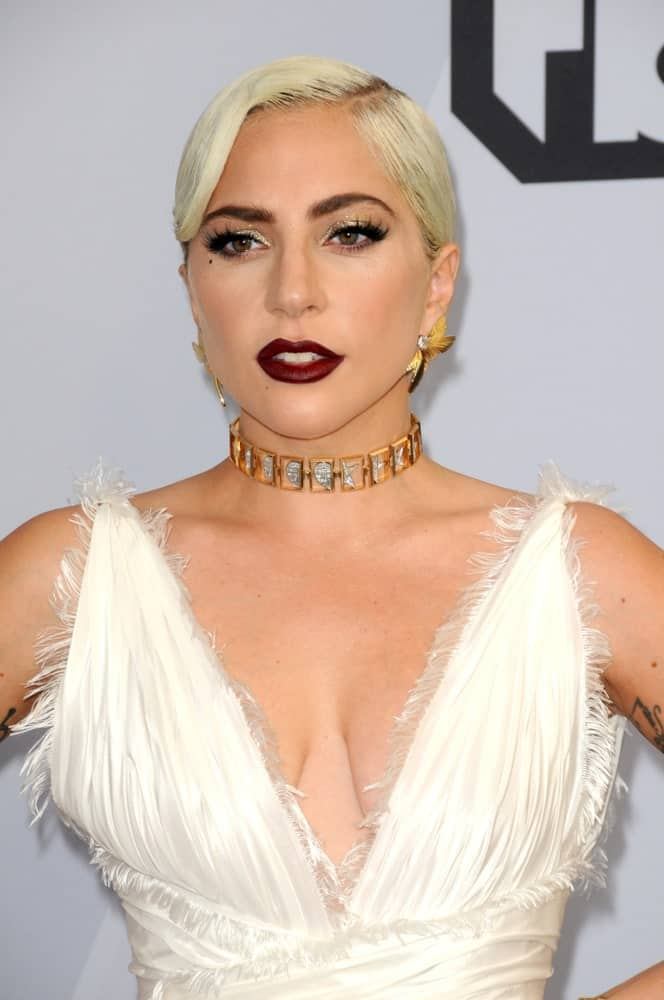 Lady Gagapaired her beautiful white dress and bold red lips with a white blond hairstyle slicked into a low bun at the 25th Annual Screen Actors Guild Awards at the Shrine Auditorium on January 27, 2019 in Los Angeles, CA.