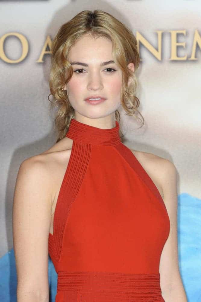 Lily James wore a stunning red dress at an event in Milan, Italy on December 25, 2017. She paired this with a sandy blonde ponytail hairstyle with curly side bangs.