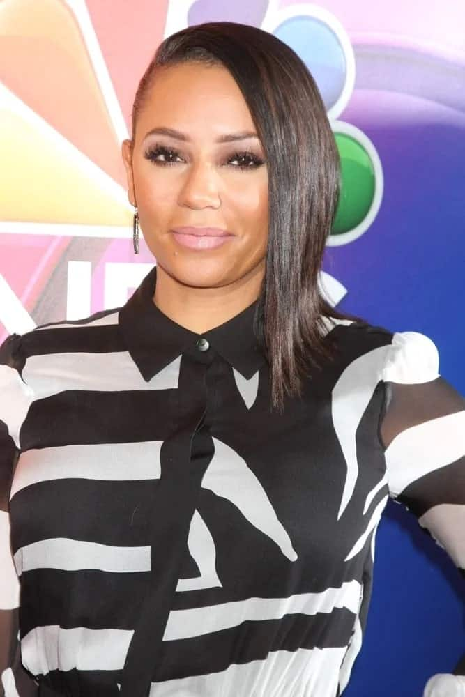 Mel B wears a zebra-patterned top paired with wide black trousers and pinned her dark hair up in a quirky side-swept half up half down style at the NBCUniversal TCA Press Day Winter 2016 on January 13, 2016.