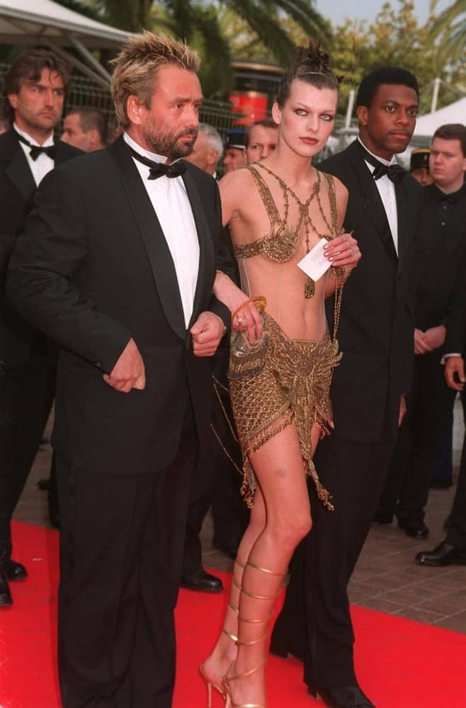 On May 7, 1997, Milla Jovovich, Chris Tucker and Luc Besson were at the 1997 Cannes Film Festival. Jovovich was stunning in her sheer dress that she paired with a slicked back top knot bun hairstyle.