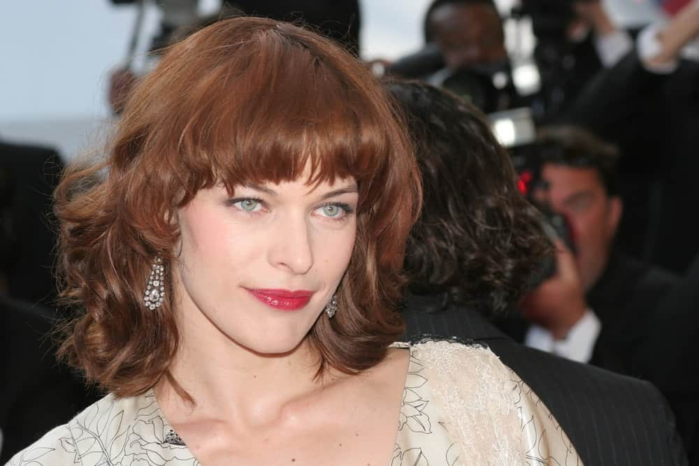Milla Jovovich attended the screening of 'Three Burials of Melquiades Estrada' at the Grand Theatre during the 58th Cannes Film Festival on May 20, 2005 in Cannes, France. She was stunning in her beige dress and tousled shoulder-length hair with bangs and a reddish tone.