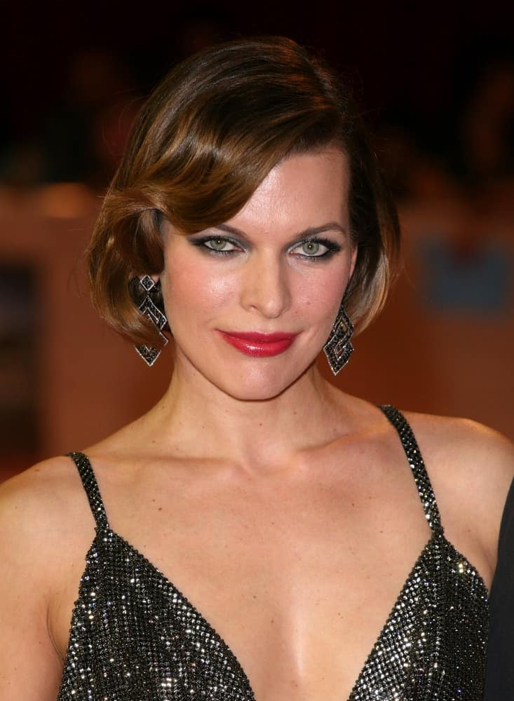 Milla Jovovich attended the UK Premiere of The Three Musketeers, at Westfield, London on October 4, 2011. She was charming in a black dress that she paired with chin-length brunette hairstyle with layers and bangs.
