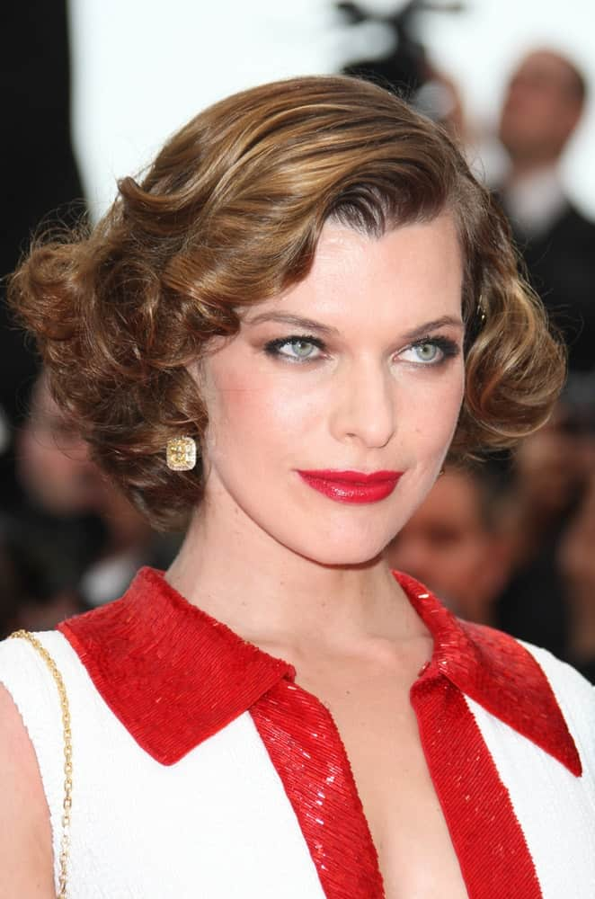 Milla Jovovich was at the 'La Conquete' Premiere, 2011 Cannes Film Festival on May 18,2011. Her red lips were a perfect match for her dress and chin-length curly hairstyle with side-swept bangs,