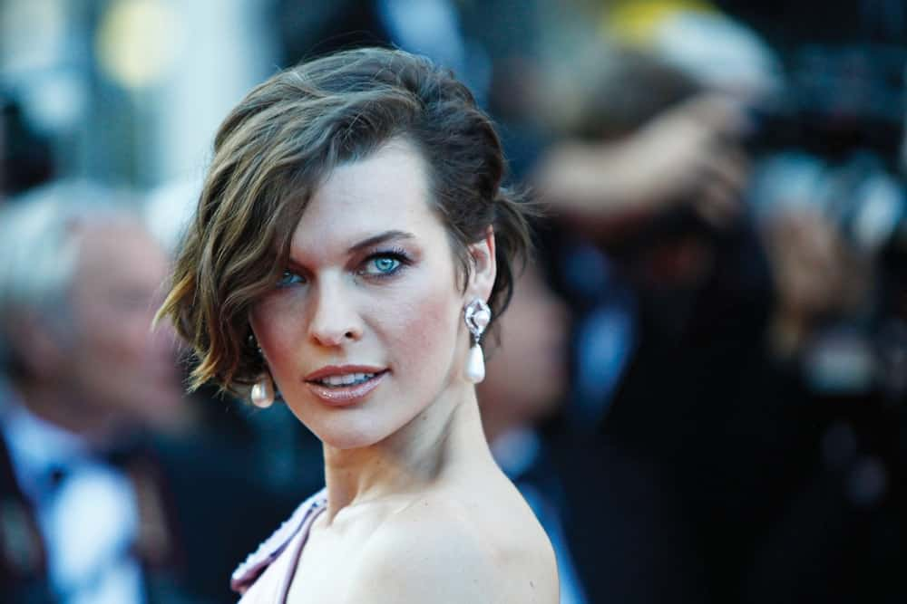 Mila Jovovich attended the 'On The Road' Premiere at Palais des Festivals on May 23, 2012 in Cannes, France. She was quite elegant in her pink dress and brunette bun hairstyle that has loose, side-swept and highlighted bangs.