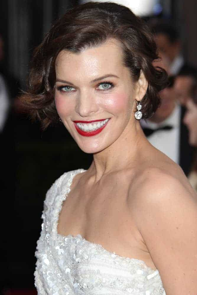 Milla Jovovich was at the 84th Academy Awards at the Hollywood & Highland Center on February 26, 2012, in Los Angeles, CA. She was lovely in a white dress, red lips, and tousled chin-length hairstyle with side-swept wavy bangs.