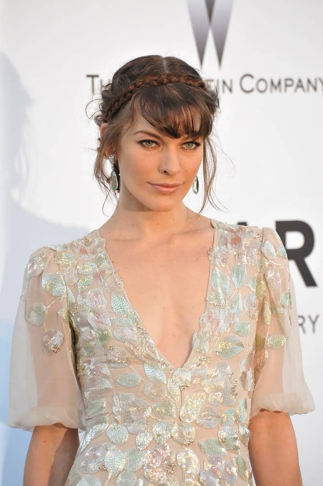 Milla Jovovich was at the amfAR's 20th Cinema Against AIDS Gala at the Hotel du Cap d'Antibes, France on May 23, 2013, in Antibes, France. She was charming in a sheer white dress and her hair was incorporated with braids, bangs and loose tendrils in an upstyle.