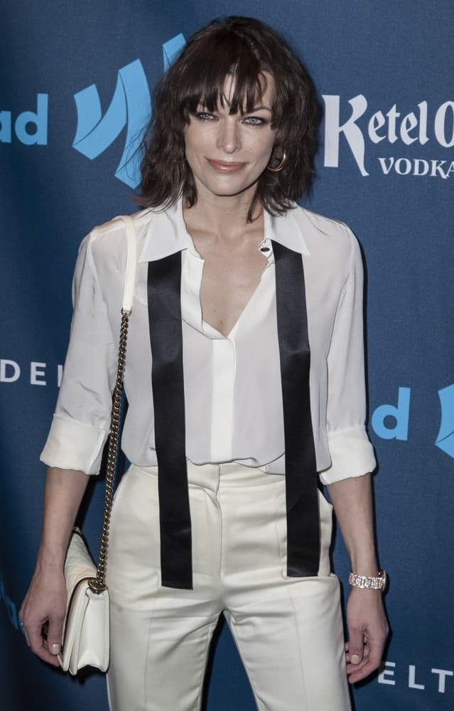 Milla Jovovich attended the 24th annual GLAAD Media awards at The New York Marriott Marquis on March 16, 2013 in New York City. She wore a white semi-formal outfit with her shoulder-length brunette hairstyle that has a slight tousle and layered bangs.