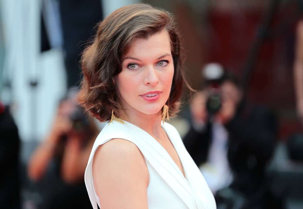 Milla Jovovich attended the 'Cymbeline' Premiere during the 71st Venice Film Festival at Sala Grande on September 03, 2014 in Venice, Italy. She paired her elegant white outfit with a shoulder-length tousled brunette hairstyle that has subtle waves and highlights.