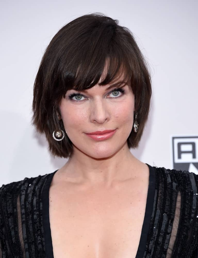 Milla Jovovich attended the American Music Awards 2016 on November 20, 2016 in Hollywood, CA. She paired her black dress with a chin-length hairstyle that has dark bangs and layers.