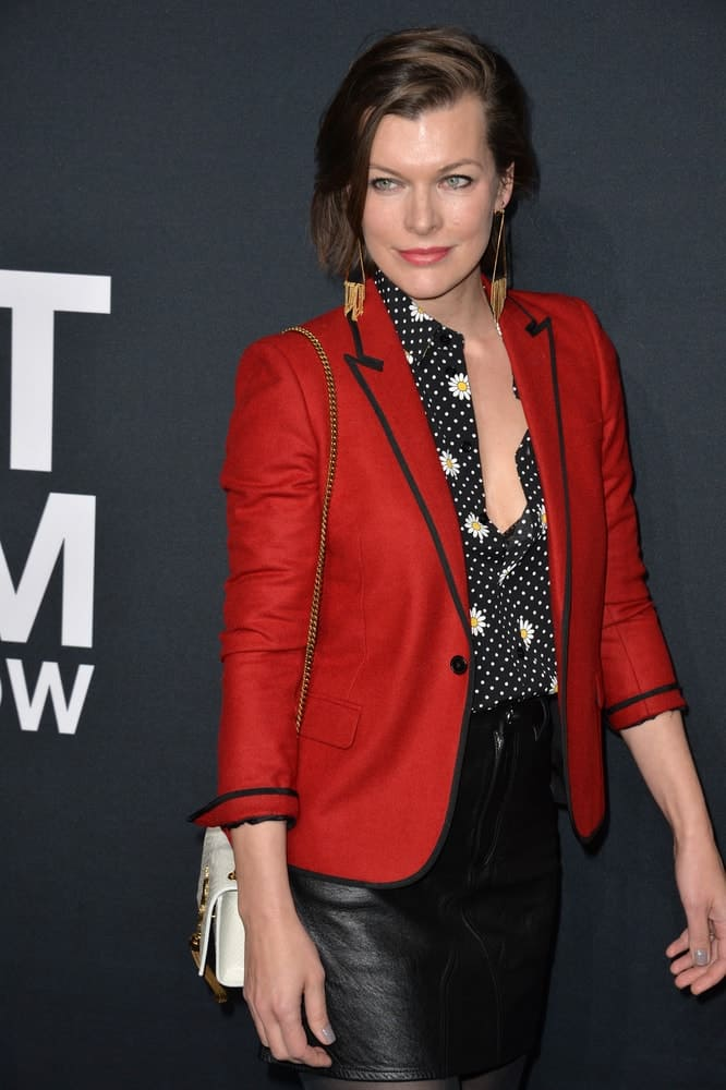 On February 10, 2016, actress Milla Jovovich was at the Saint Laurent at the Palladium fashion show at the Hollywood Palladium. She wore a red jacket over her black outfit and topped it with a slick side-swept chin-length brunette hairstyle.
