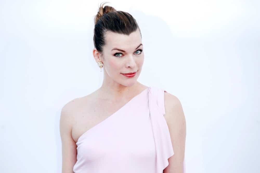 Milla Jovovich was at the amfAR Gala Cannes 2018 at Hotel du Cap-Eden-Roc on May 17, 2018 in Cap d'Antibes, France. She wore a white gown that she paired with her slicked-back bun hairstyle.