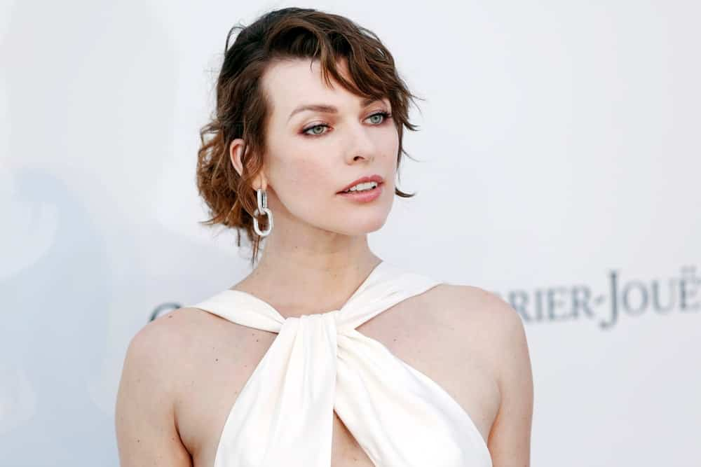 Milla Jovovich attended the amfAR Cannes Gala 2019 at Hotel du Cap-Eden-Roc on May 23, 2019 in Cap d'Antibes, France. She was stunning in a white dress that she paired with a messy dark brunette bun hairstyle that has side-swept bangs.