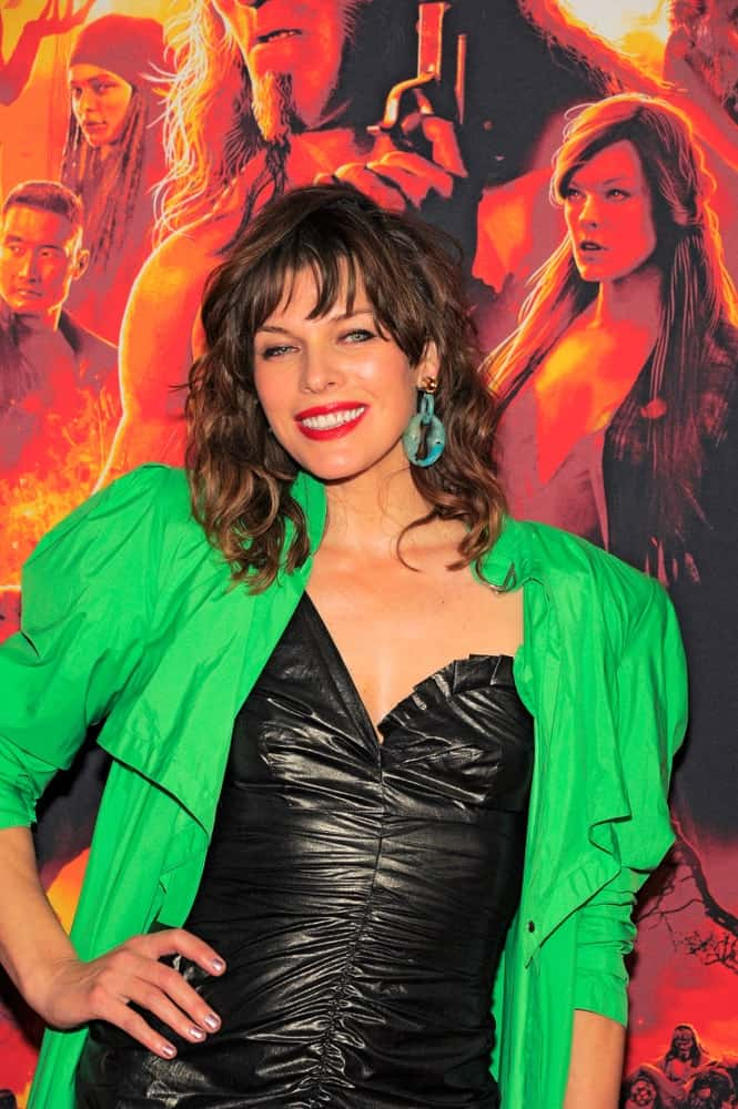 Milla Jovovich attended the 'Hellboy' New York Screening at AMC Lincoln Square Theater on April 09, 2019 in New York City. She wore a green jacket over her leather dress and paired it with a shaggy layered hairstyle with highlights and bangs.
