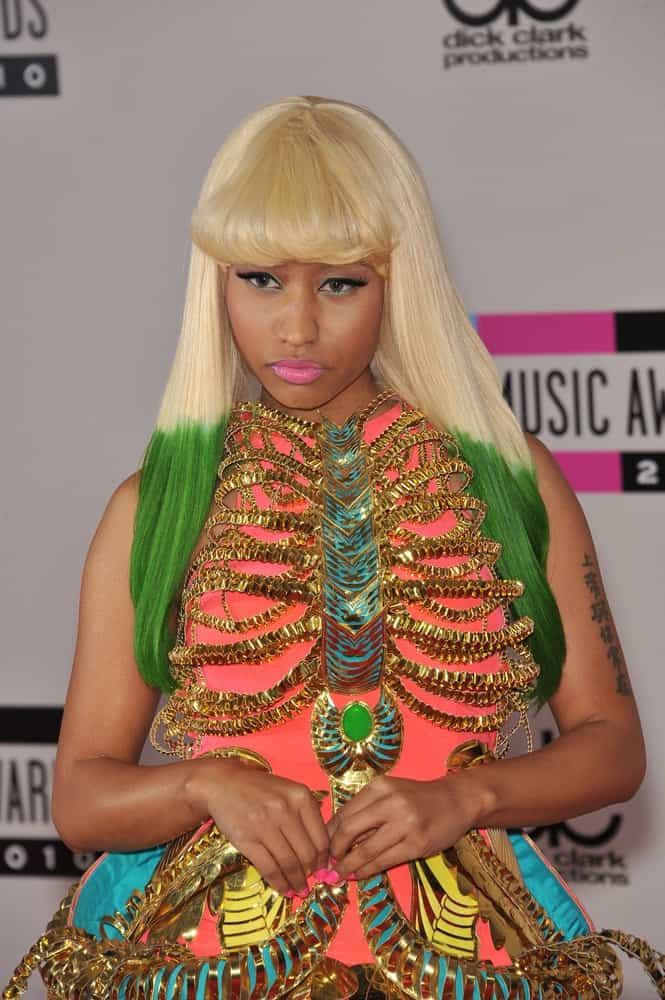 Nicki Minaj attended the 2010 American Music Awards at the Nokia Theatre L.A. Live in downtown Los Angeles on November 21, 2010 Los Angeles, CA. She came wearing a colorful artistic dress that she paired with her long and straight white hair with green dye at the tips and blunt tousled bangs.