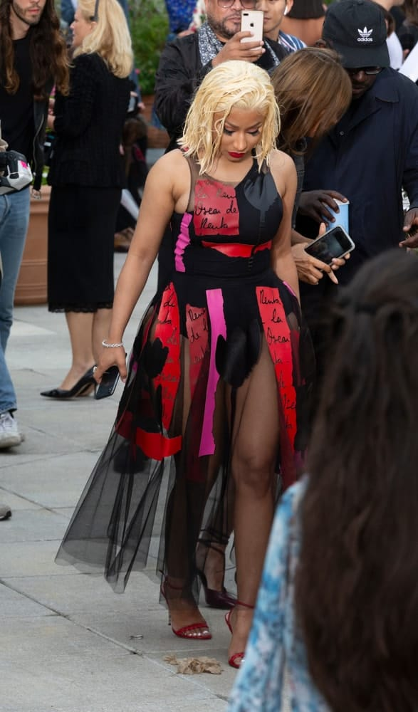 On September 11, 2018, Nicki Minaj attended the runway for Oscar De La Renta during New York Fashion Week Spring/Summer 2019 at Spring Studios Terrace. She was seen wearing a fashion forward red and black dress to match her shoulder-length blond hairstyle with a tousled wet-look finish.