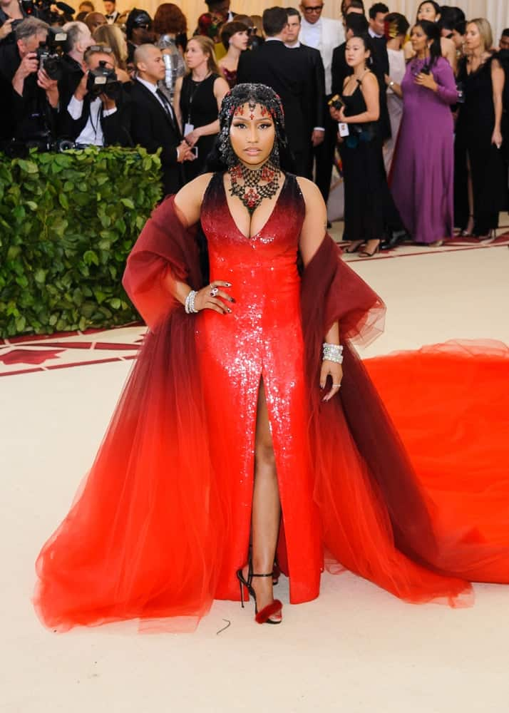 Nicki Minaj attended the 2018 Metropolitan Museum of Art Costume Institute Benefit Gala on May 7, 2018 at the Metropolitan Museum of Art in New York, New York. She wore a lovely red and black dress to go with her straight and long black hair incorporated with gemstones.