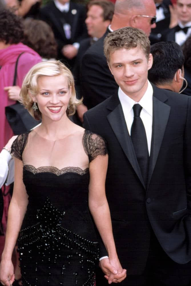 Reese Witherspoon and Ryan Phillippe were at the Academy Awards on March 24, 2002 in Los Angeles, California. Witherspoon wore a lovely and elegant black dress to go with her short layered blond hairstyle that has curls at the tips and side-swept bangs.
