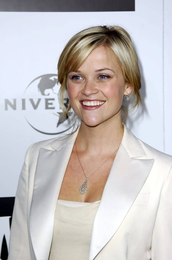Reese Witherspoon attended the WICKED Opening Night Hosted by Universal Pictures in Pantages Theatre, Los Angeles, CA on June 22, 2005. She wore an all-white smart outfit with her loose and messy blond bun hairstyle that has loose tendrils and bangs.