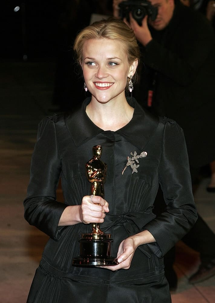 Reese Witherspoon was at the Vanity Fair Oscar Party held at the Mortons Restaurant in West Hollywood, Los Angeles, CA on March 05, 2006. She came holding her trophy while wearing a lovely black dress with her hair swept up into a blond bun hairstyle.