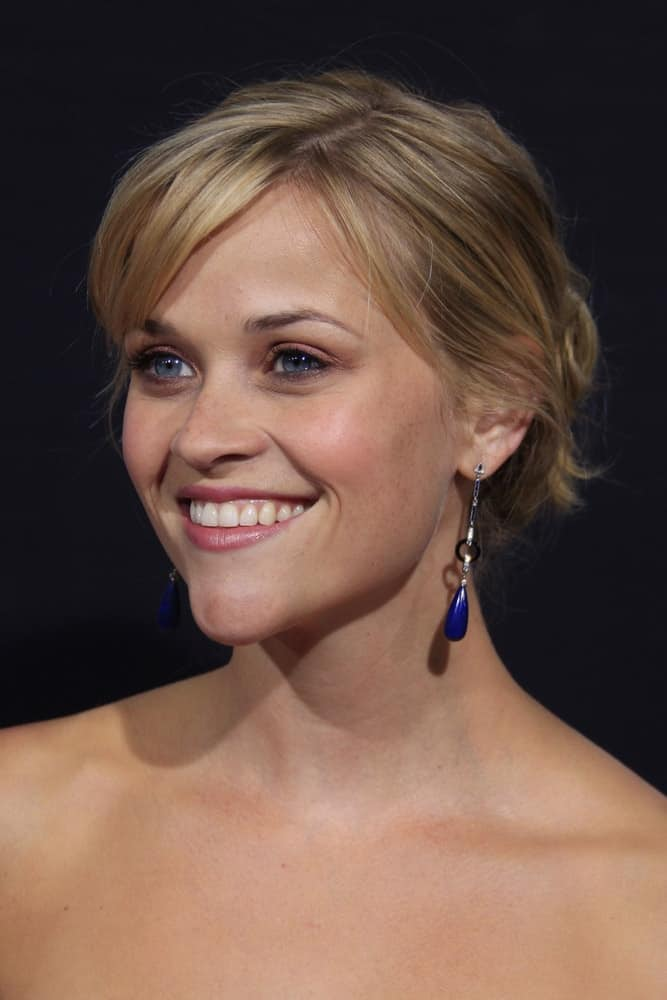 Reese Witherspoon flashed her iconic and brilliant smile that she paired with a couple of charming earrings and a messy bun hairstyle with side-swept bangs at the Rendition Premiere in Beverly Hills, California on October 10, 2007.
