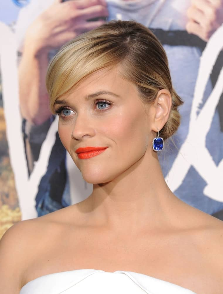 Reese Witherspoon wore an elegant white strapless dress to go with her neat blond low bun hairstyle with long and loose side-swept bangs when she arrived at the