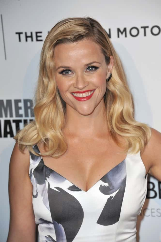 On October 21, 2014, Reese Witherspoon wore a stunning white dress that complemented her highlighted and loose side-swept wavy blond hairstyle at the 28th Annual American Cinematheque Award Gala honoring Matthew McConaughey at the Beverly Hilton Hotel.