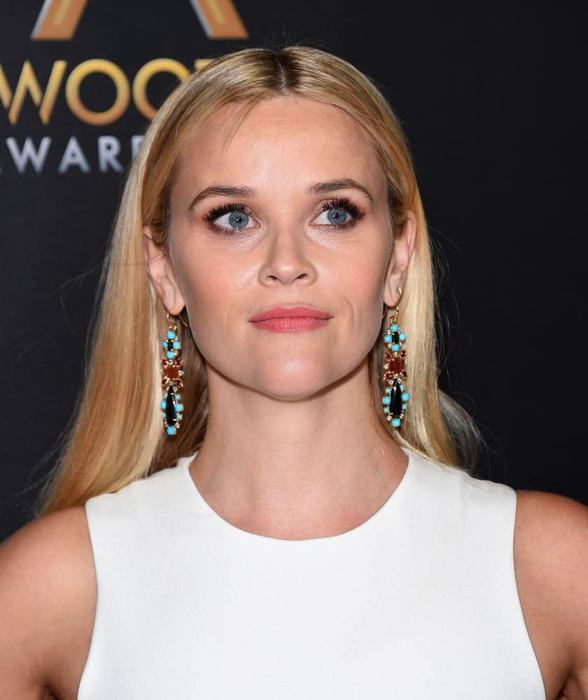 Reese Witherspoon paired her simple white outfit with a long and straight blond hairstyle center-parted and tucked behind her ears at the Hollywood Film Awards 2015 on November 1, 2015 in Hollywood, CA.