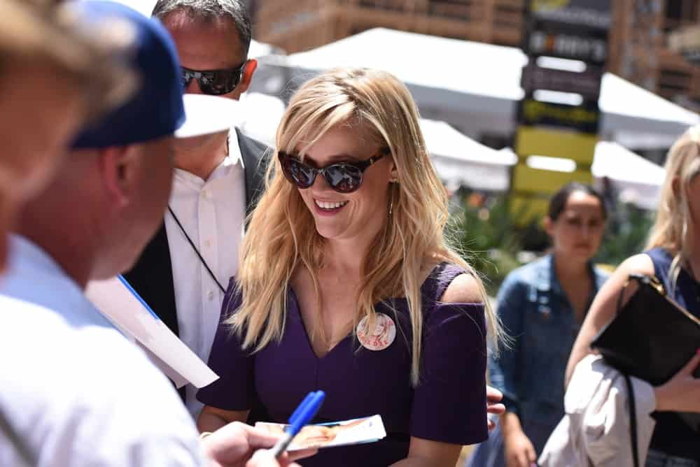 Reese Witherspoon signed some autographs at the Goldie Hawn & Kurt Russell Hollywood walk of fame Star receiving ceremony at the Hollywood Blvd on May 4, 2017 in Los Angeles, CA. She came wearing a purple dress to pair with her tousled and layered loose blond hair with bangs.