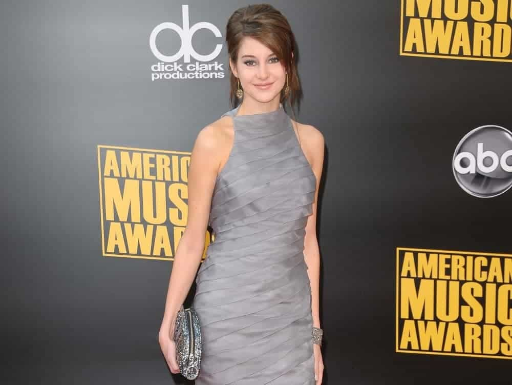 Shailene Woodley was at the 2008 American Music Awards. Nokia Theatre, Los Angeles, CA on November 23, 2008. She was stunning in a gray dress that she topped with a messy bun hairstyle incorporated with long side-swept bangs.