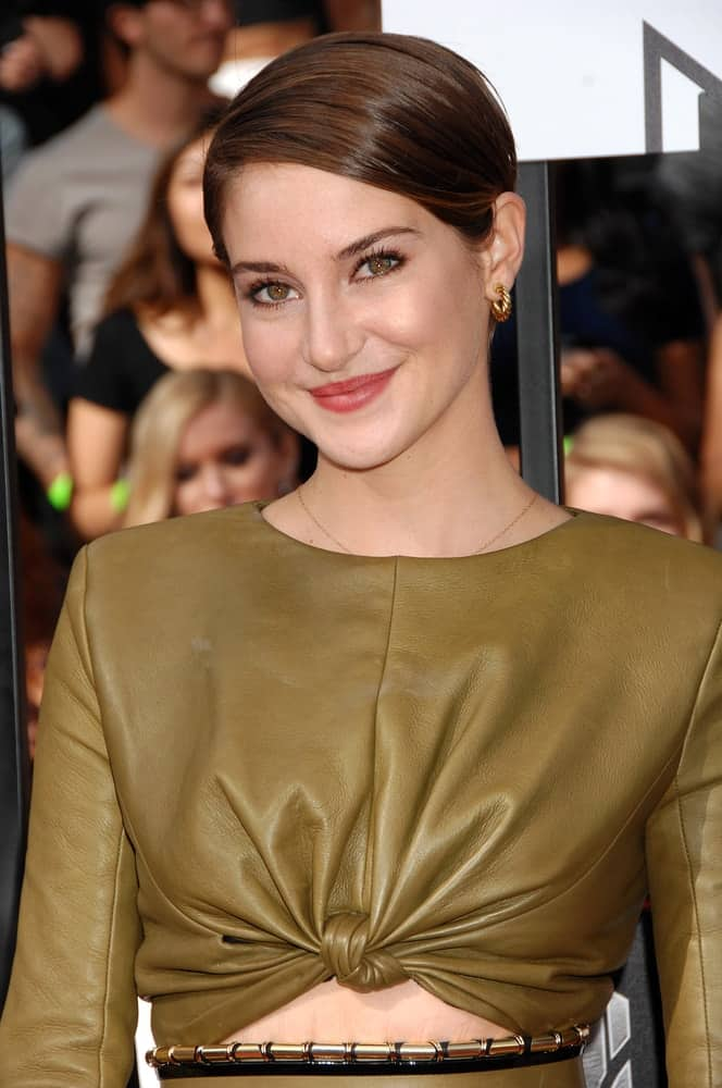 Shailene Woodley was at the 2014 MTV MOVIE AWARDS on April 13, 2014 in Los Angeles, CA. She was seen wearing a green leather dress with her slick side-parted brunette hairstyle.
