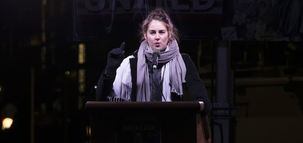 On January, 19 2017, Shailene Woodley spoke onstage during the We Stand United NYC Rally outside Trump International Hotel & Tower. She wore her winter outfit with her makeup-less face and messy bun hairstyle with loose tendrils.