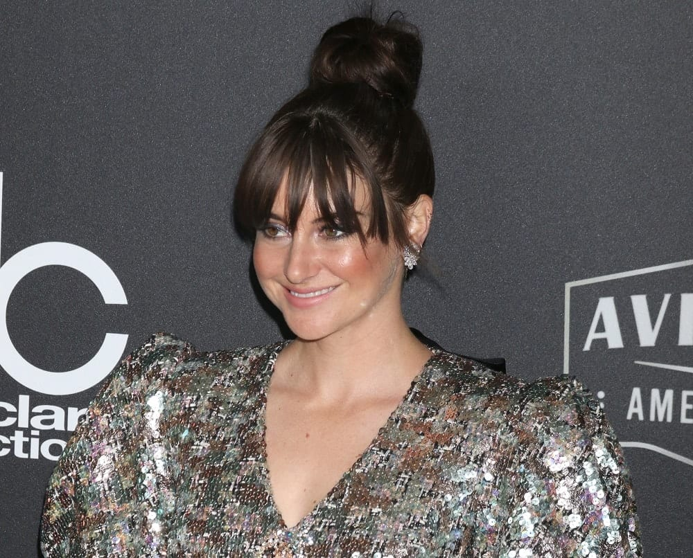 Shailene Woodley was at the Hollywood Film Awards 2018 at the Beverly Hilton Hotel on November 4, 2018 in Beverly Hills, CA. She posed for the cameras in a shiny dress that went well with her raven top knot bun hairstyle with bangs.