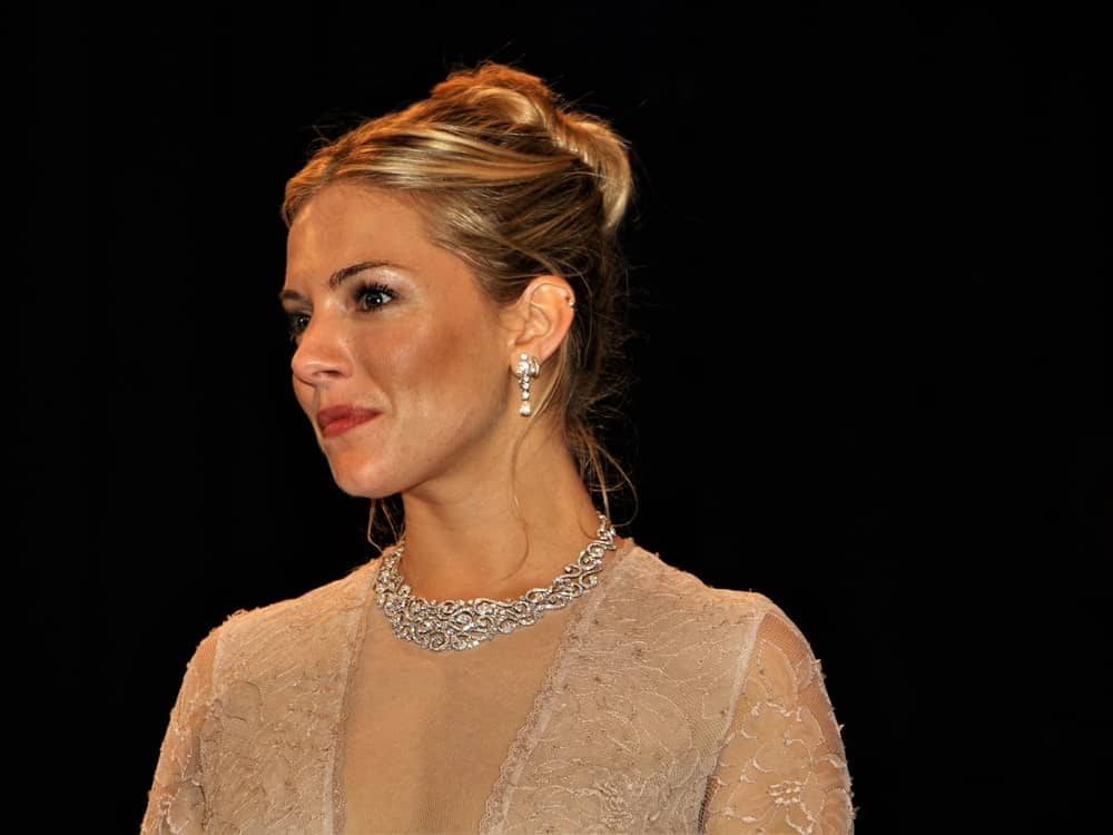 Sienna Miller shines in a glam updo that's paired with silver earrings and a collar necklace during UNESCO-Gala in 2010 at Dusseldorf, Germany.