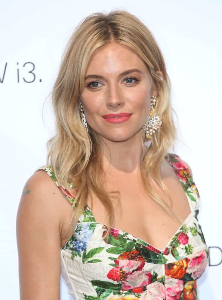 Sienna Miller made an appearance at the BMW i3 Launch Party on July 29, 2013. She wore a floral dress and a loose, layered hairstyle with subtle highlights.
