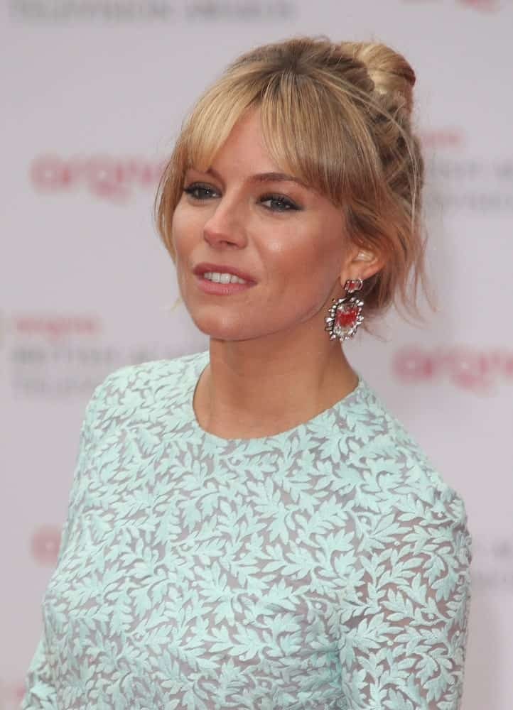 Sienna Miller pulled back her hair into a high bun with curtain bangs at the 2013 TV BAFTA Awards held on December 5, 2013. She finished the look with a long-sleeved dress and gorgeous earrings.