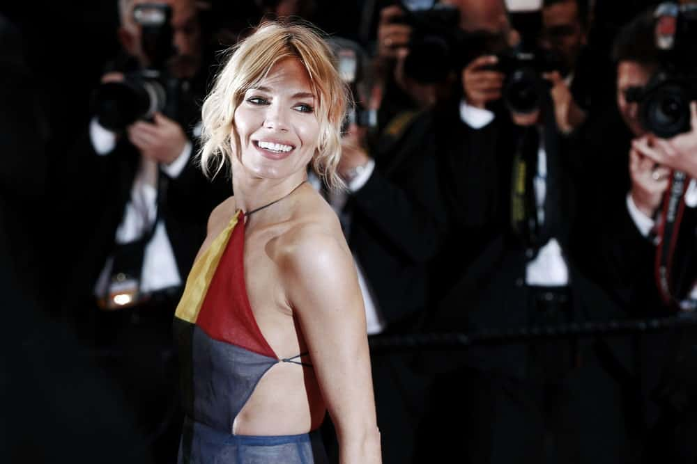 Sienna Miller looking all sexy and sultry in a halter dress and a loose updo with thick, curly tendrils as she attends the Premiere of 'The Sea Of Trees' on May 16, 2015, in Cannes, France.
