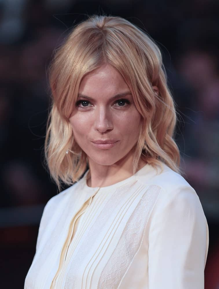 Sienna Miller arrived for the High-Rise premiere on October 9, 2015, with a pinned shoulder-length hairstyle complemented with curtain bangs.