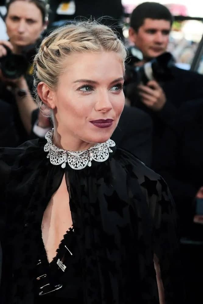 Sienna Miller made a surprising appearance in a black semi-sheer gown featuring a dramatic cape. Her double braid bun hairstyle complements her elegant outfit during the 'Carol' premiere held on May 17, 2015.
