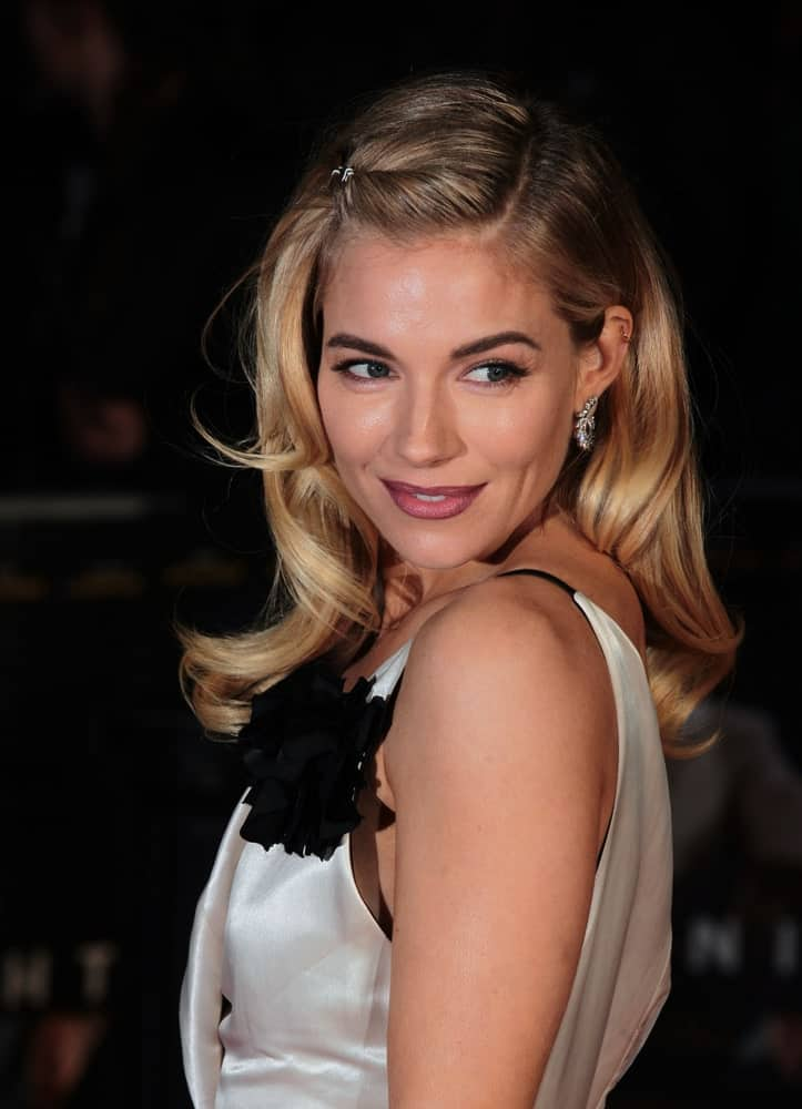 Sienna Miller looks sensational wearing her silky monochrome dress and her blonde waves were styled in a loose side-part with one side pinned up as she attends the Live By Night European film premiere on January 11, 2017.
