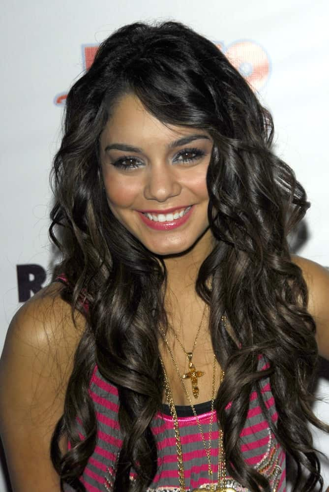 Vanessa Anne Hudgens wore a striped pink casual top with her long and loose tousled curly raven hairstyle with long side-swept bangs at the Radio Disney Totally 10 Birthday Concert on July 22, 2006 at Anaheim Pond in Anaheim, CA.