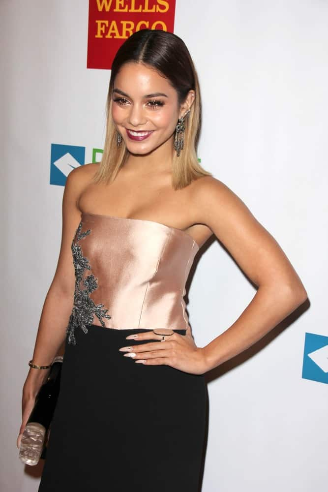 Vanessa Hudgens attended the Voices On Point at Century Plaza Hotel on September 13, 2014 in Century City, CA. She came wearing an elegant strapless dress that she paired with her loose and straight highlighted hairstyle tucked behind her ears.