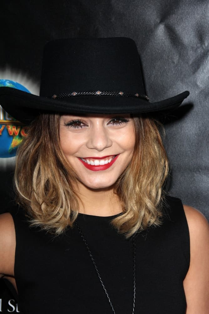 Vanessa Hudgens wore a simple black outfit with her black cowboy hat and shoulder-length highlighted hairstyle with a slight tousled finish at the Universal Studio's Halloween Horror Nights 2014 Eyegore Award at Universal Studios on September 18, 2014 in Los Angeles, CA.