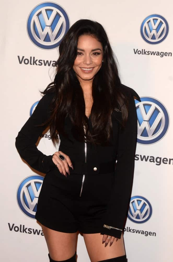 Vanessa Hudgens wore a very fashionable black romper to match with her long and loose wavy hairstyle that has a slight tousle, waves and subtle highlights at the Volkswagen's Annual Holiday Drive-In on the Goya Studios on November 30, 2018 in Los Angeles, CA.