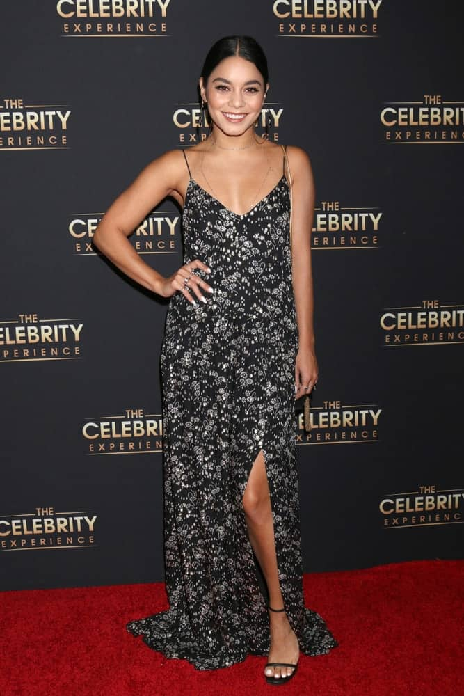 Vanessa Hudgens wore a lovely and stunning long floral black dress with her neat and slick heairstyle at the The Celebrity Experience at the Universal Hilton Hotel on August 12, 2018 in Universal City, CA.